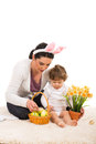 Mother and son arrange easter basket toddler boy sitting together on fur carpet Stock Photos