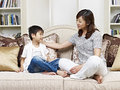 Mother and son asian having a conversation on couch at home Stock Image