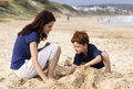 Mother and son on the beach a her playing they are digging in sand Royalty Free Stock Photos