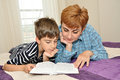 Mother and son in bed reading a book lying together Stock Photo