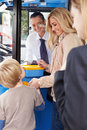 Mother and son boarding bus and buying ticket from the driver whilst smiling at each other Stock Photography
