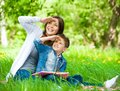 Mother and son with book cover eyes in park Royalty Free Stock Photos