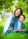 Mother and son with book in park pointing hand gesture Stock Photo