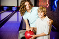 Mother and son in a bowling alley, holding red bowling ball Royalty Free Stock Photo