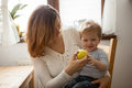 Mother and son eating an apple at the kitchen Royalty Free Stock Photo