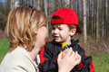 Mother and son with flowers in red cap outdoors Stock Photo
