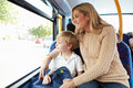 Mother and son going to school on bus together looking out the window smiling Royalty Free Stock Image