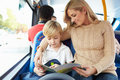 Mother and son going to school on bus together reading a book Royalty Free Stock Images