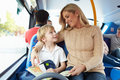 Mother and son going to school on bus together smiling at each other whilst reading a book Stock Image
