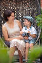 Mother and son having relax on cane-chair outdoors Royalty Free Stock Photo