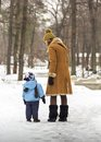 Mother and son her walking in the park in a lovely winter day Royalty Free Stock Image