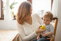Mother and son at the kitchen eating an apple Royalty Free Stock Photo