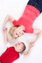 Mother and the son lie on a floor having joined hands top view Stock Image