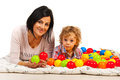 Mother and son lying bed with balls on a many colorful against white background Stock Photography