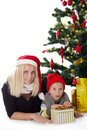 Mother and son lying under christmas tree happy over white Stock Images