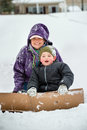 Mother and son playing in snow using cardboard to slide down hill box Stock Photos