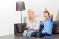Mother and son playing a video game beautiful women her teenage at home sitting on couch Stock Photos