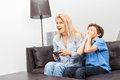 Mother and son playing a video game beautiful women her teenage at home sitting on couch Stock Photography