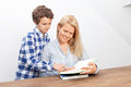 Mother and son are reading a is a book her is standing behind her showing her something in the book Royalty Free Stock Image