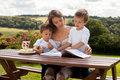 Mother and son, reading a book outdoor, summer day Royalty Free Stock Photos