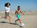 Mother and son running on beach with ball Royalty Free Stock Photo