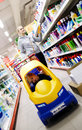 Mother and son shopping in a supermarket with the little boy riding colourful plastic toy car attached to the Royalty Free Stock Images