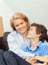 Mother and son sitting on a couch beautiful women her teenage at home cuddling Royalty Free Stock Image