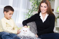 Mother and son sitting on the couch and caressing a white persia persian cat Royalty Free Stock Images