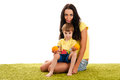 Mother and son sitting on the green grass with oranges happy Royalty Free Stock Photography