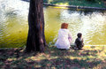 Mother and son sitting by the lake admiring landscape Royalty Free Stock Image