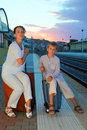 Mother and son sitting on platform of railway Stock Images