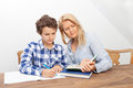 Mother and son studying a boy is doing his homework his is helping him with it they look very happy Stock Photo