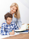 Mother and son studying a boy is doing his homework his is helping him with it they look very happy Royalty Free Stock Photography