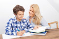 Mother and son studying a boy is doing his homework his is helping him with it they look very happy Stock Image