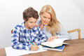 Mother and son studying a boy is doing his homework his is helping him with it they look very happy Stock Images