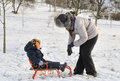 Mother and son tobogganing in the snow with little boy sitting on sled as his pulls it along wintry landscape Stock Photos