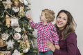 Mother and son under christmas tree are looking at Royalty Free Stock Photos