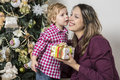 Mother and son under christmas tree are looking at Royalty Free Stock Photography