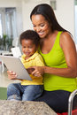 Mother and son using digital tablet in kitchen together smiling Royalty Free Stock Photo