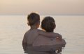 Mother and son watching the sunset her little standing chest high in a calm sea with their backs to camera Stock Image