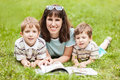 Mother and sons reading book outdoor Stock Photos