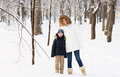 Mother and sun in warm coats walking in a snowy forest on sunny day Royalty Free Stock Images