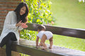 Mother support her baby daughter to make her first step Royalty Free Stock Photo