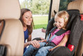 Mother takes care about her daughter in a car helps and cheers up Stock Image