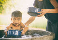 Mother is taking a bath for her son in water well. Royalty Free Stock Photo