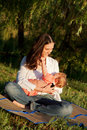 Mother taking care of baby breast feeding in the sunlight at sunset summer holiday Royalty Free Stock Image