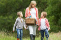 Mother taking children on picnic in countryside smiling Royalty Free Stock Images