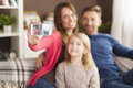 Mother taking photos of her family let s take a selfie by mobile phone Stock Photos