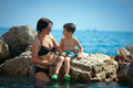 Mother talking with her son on a rocky seashore Stock Image