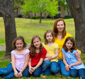 Mother teacher with daughter pupils in playground park group portrait on lawn Royalty Free Stock Photo